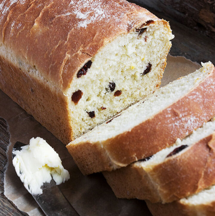 orange marmalade and dried cranberry yeast bread sliced on cutting board