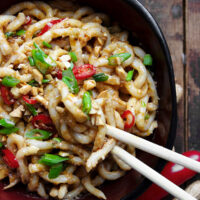 spicy peanut udon in bowl with chopsticks
