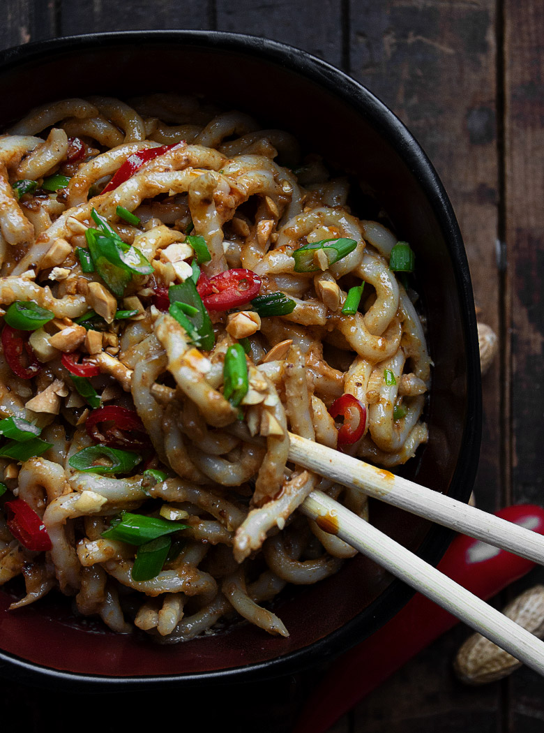 peanut udon in black bowl with chopsticks