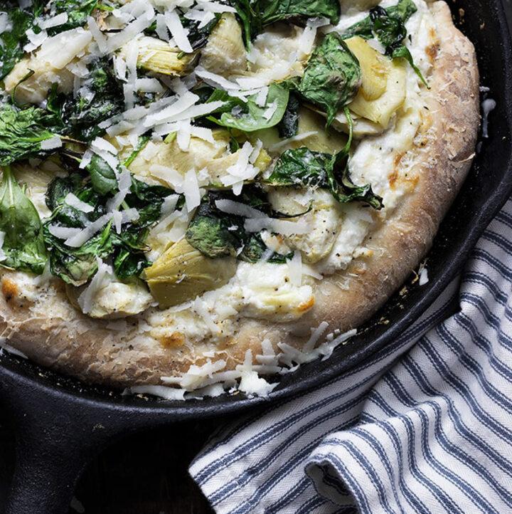 spinach artichoke pizza in skillet
