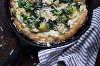 spinach artichoke pizza in a cast iron skillet