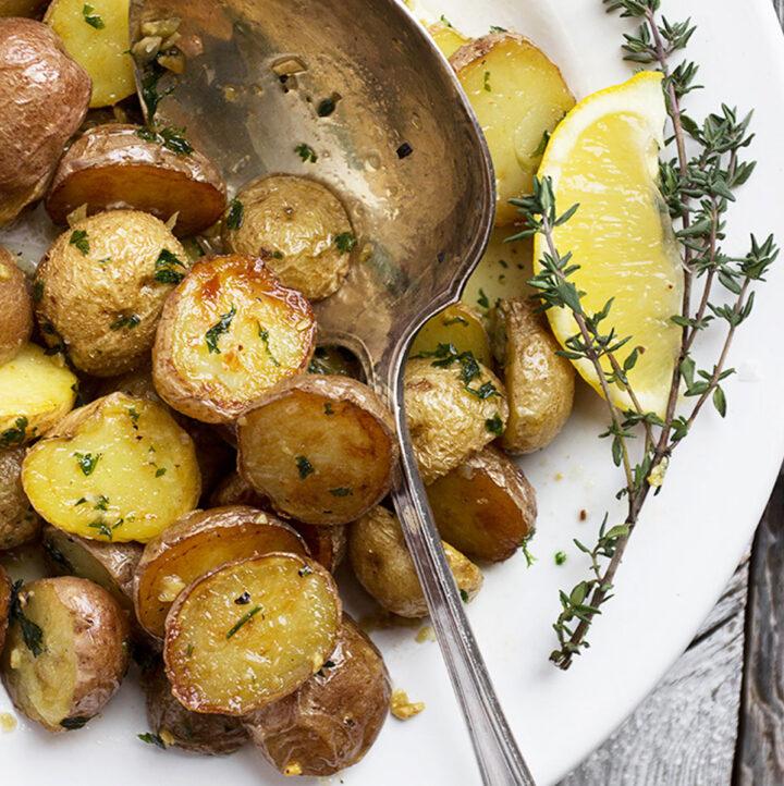 lemon garlic potatoes in white bowl with spoon