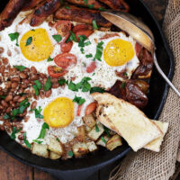 breakfast skillet in cast iron skillet with eggs potatoes and sausage