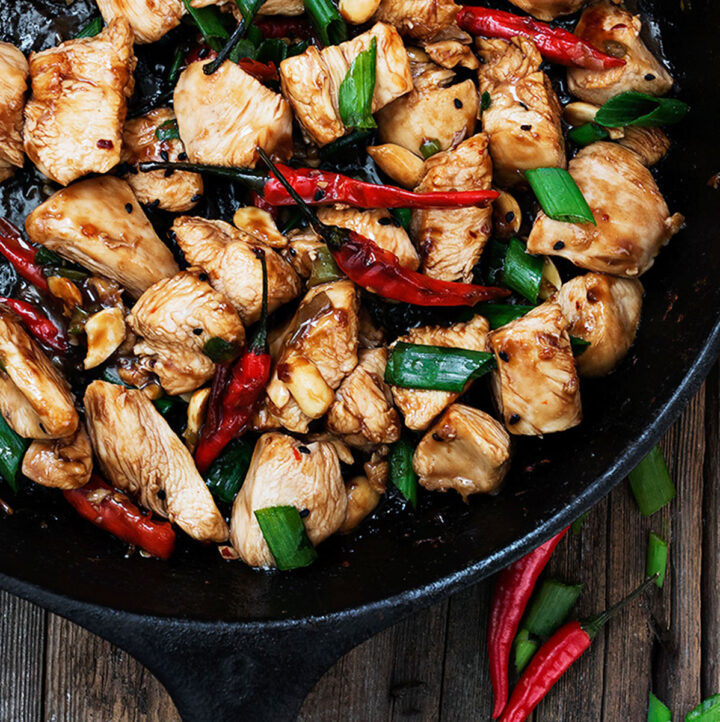 kung pao chicken in cast iron skillet with peppers
