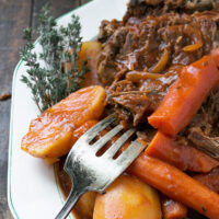 tangy tomato pot roast on plate with carrots and potatoes