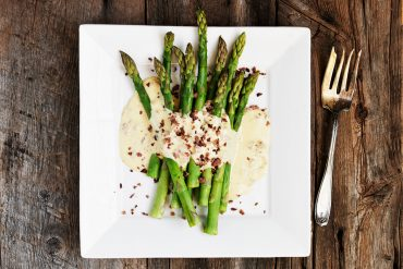 cooked asparagus on white plate with carbonara sauce and bacon garnish