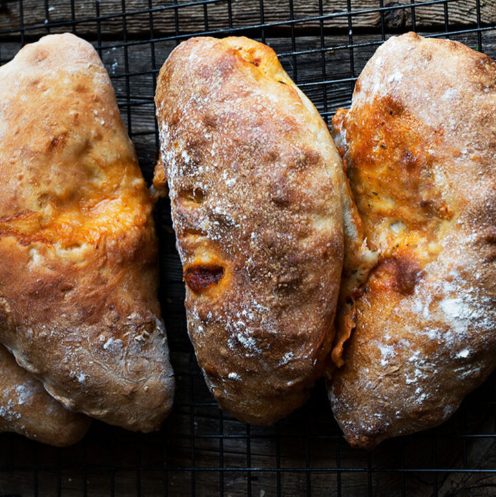 calzones lined up on dark background