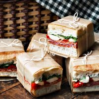 pressed picnic sandwiches in front of picnic basket