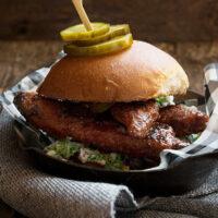 nashville hot chicken sandwich on platter with pickles
