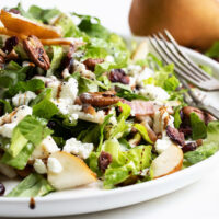 Fall pear chopped salad on white plate with pear behind