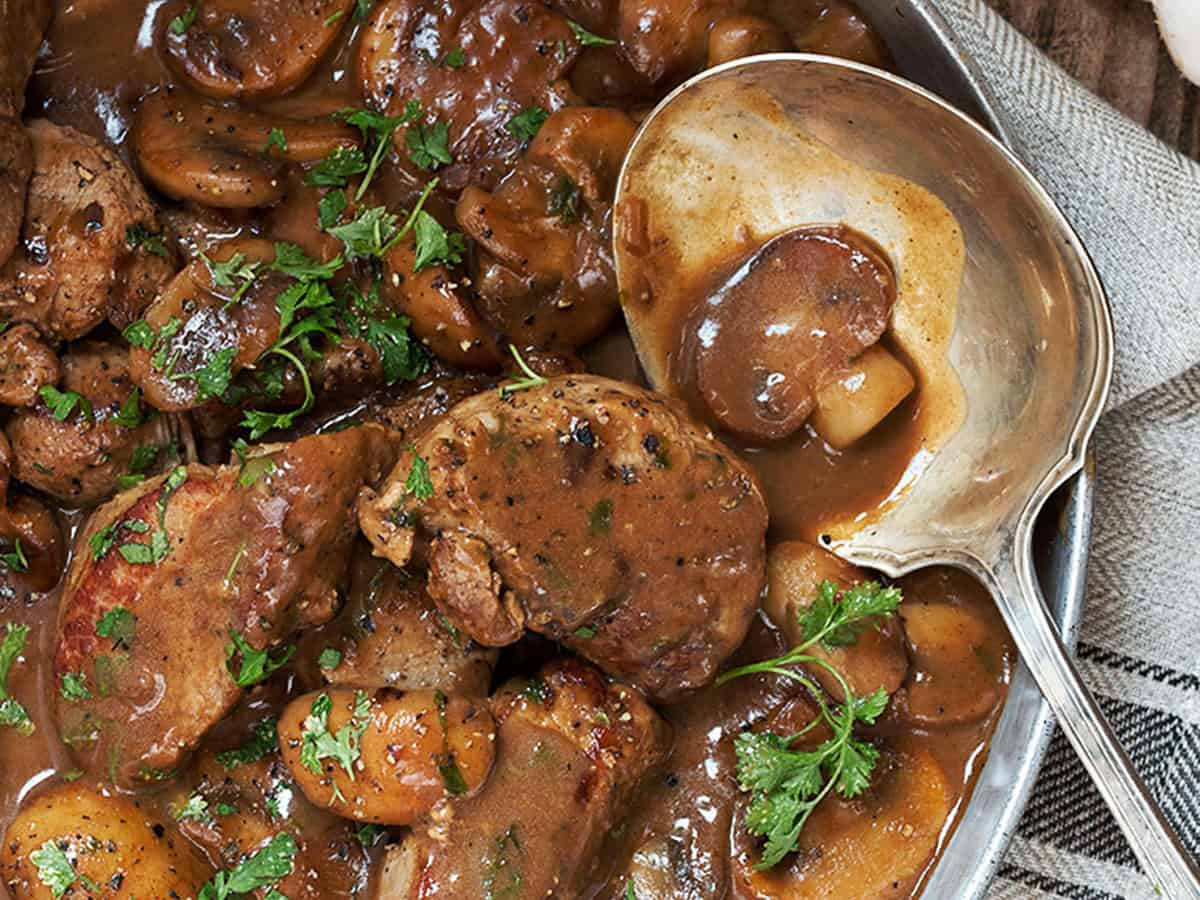 pork medallions with mushrooms and marsala sauce in pan