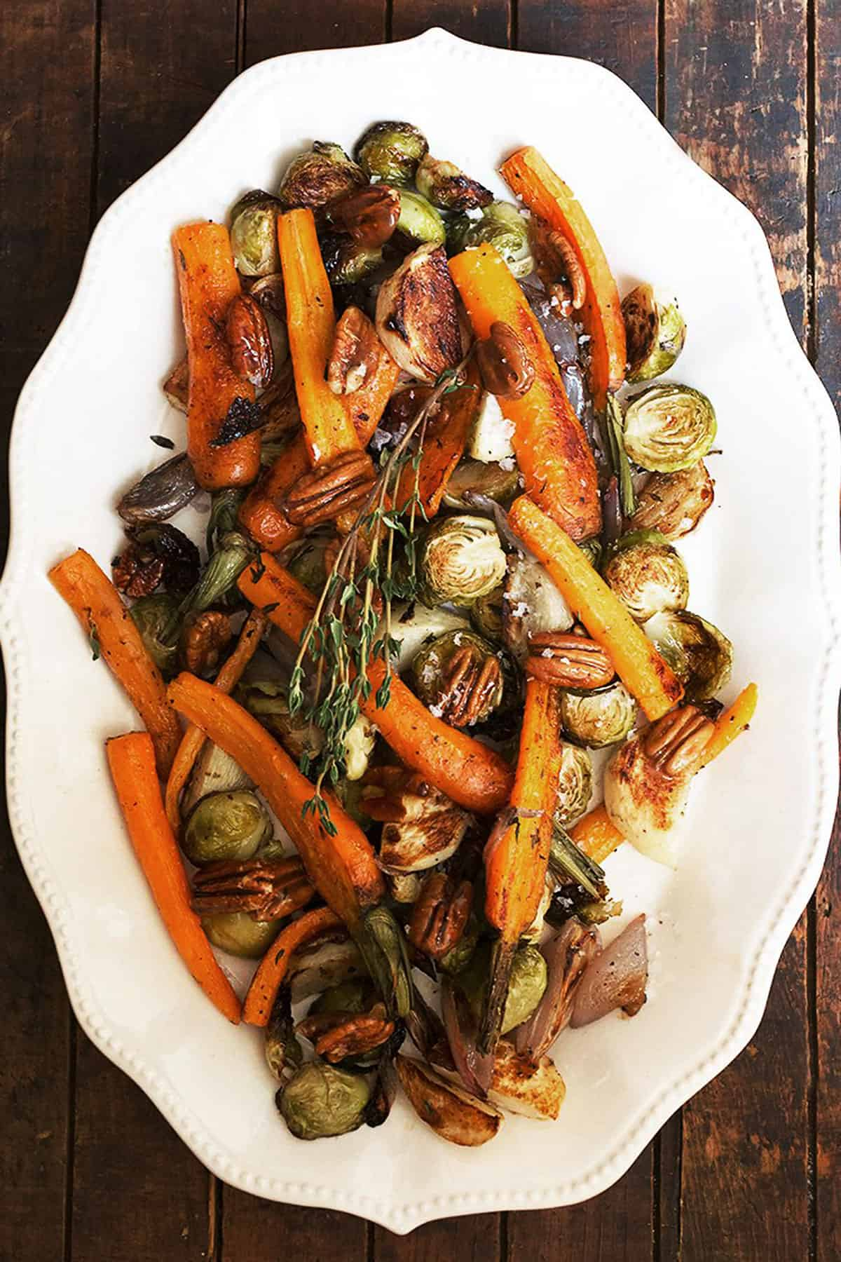 maple roasted vegetables with maple pecans on white plate