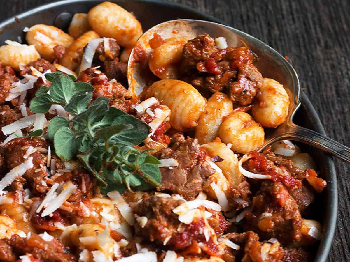 gnocchi with chorizo sausage sauce in pan with spoon
