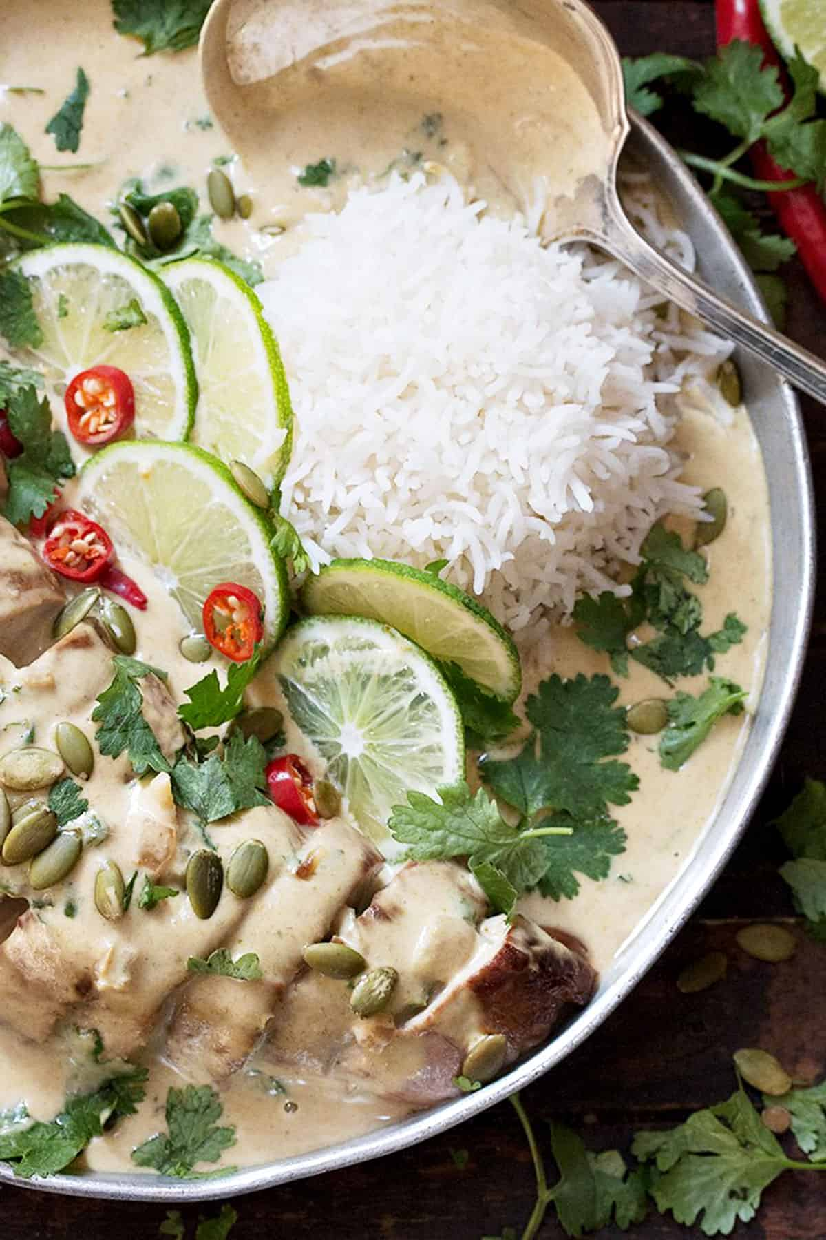 Thai green curry pork on platter with rice and limes