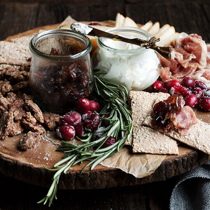 cranberry charcuterie platter on wooden round board