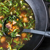 Asian-inspired pork meatball soup with bok choy in cast iron wok