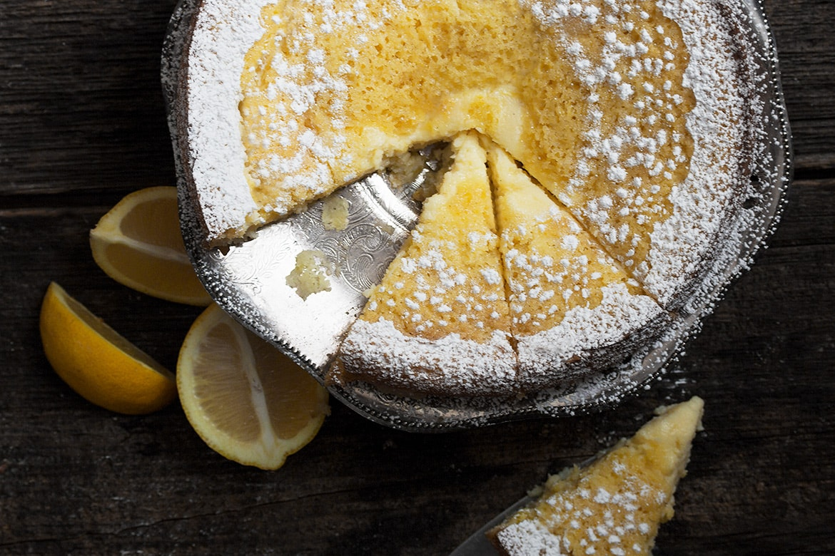 Top down view of icing sugar dusted Lemon Cream Butter Cake with a slice removed
