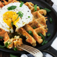 loaded potato waffles in skillet with fried egg on top