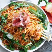 red pepper pasta on plate with prosciutto