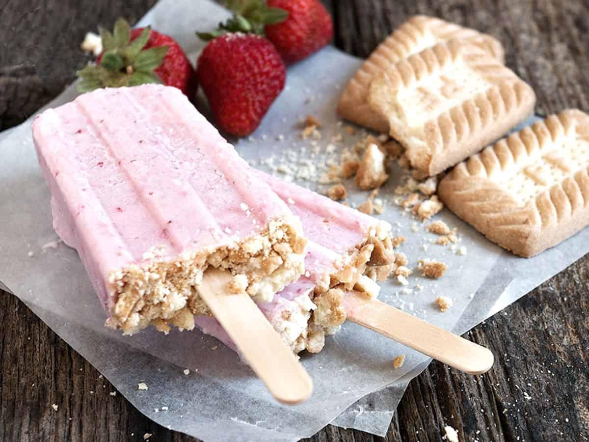 strawberry yogurt pops on parchment with strawberries