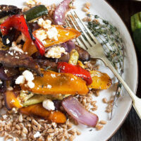farro and roasted vegetable salad on white plate with fork