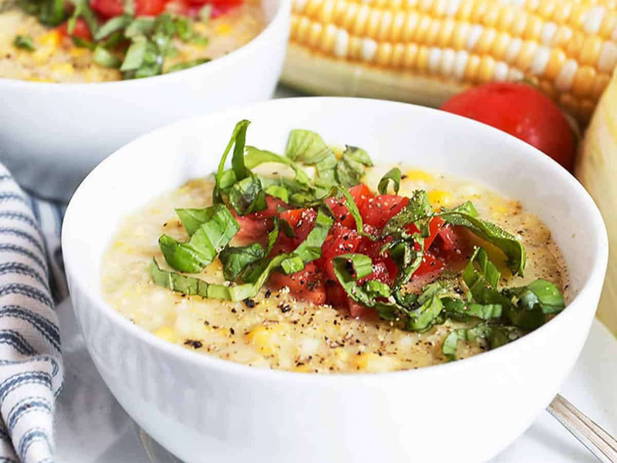 fresh corn soup in white bowls with basil and tomatoes on top