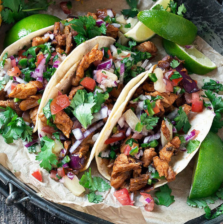 tacos al pastor on platter with lime slices