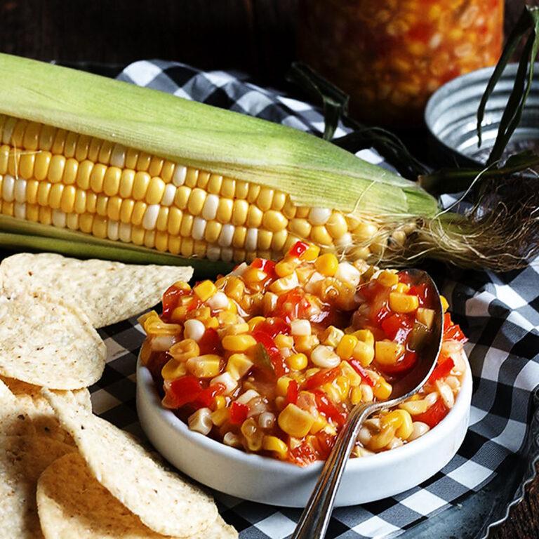 corn chile salsa in white bowl with corn cob