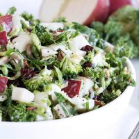 kale salad with apple in a white bowl