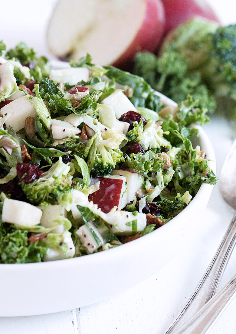 kale salad in white bowl with ingredients beside bowl