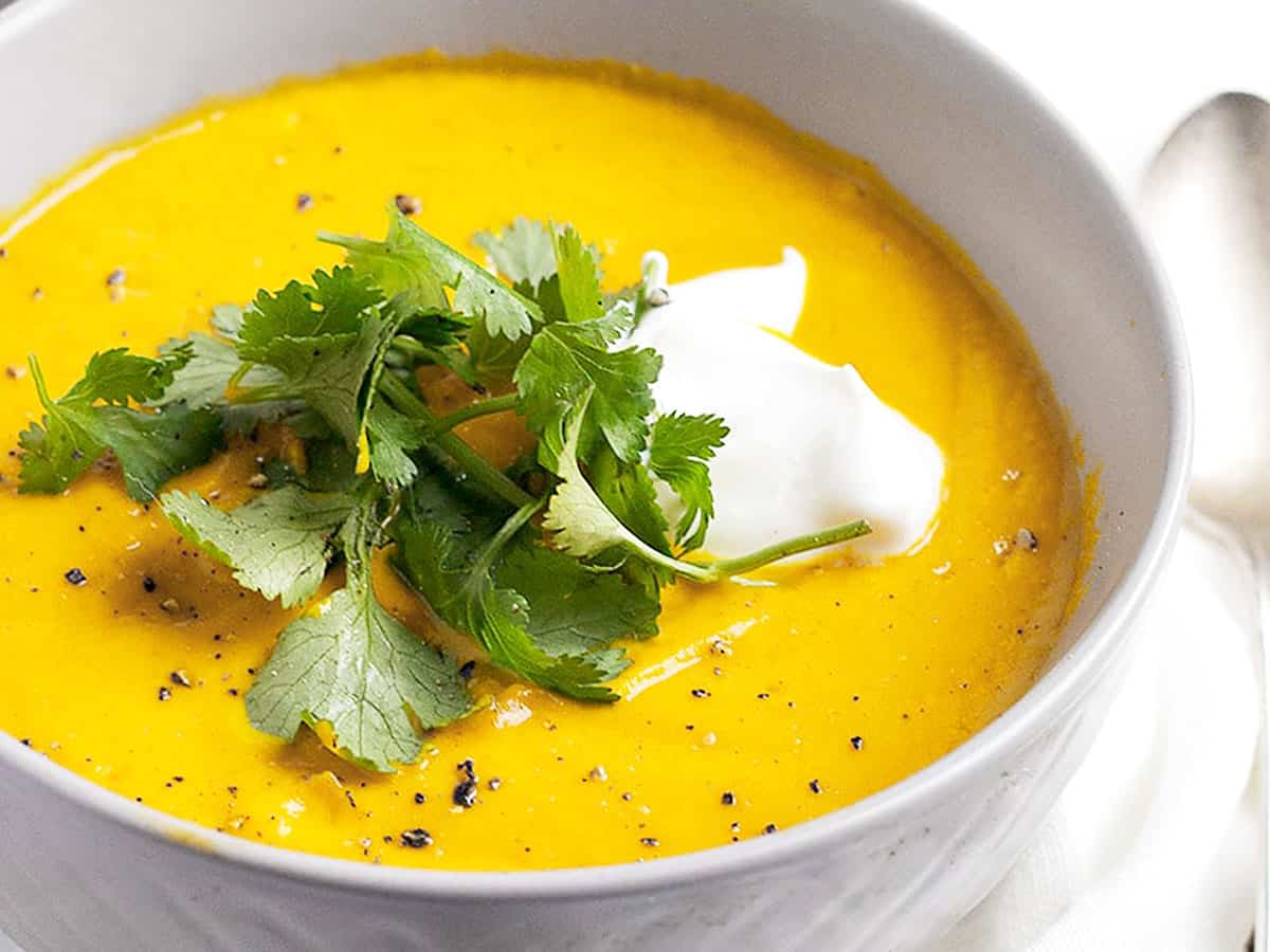 Thai carrot soup in bowls with cilantro and sour cream
