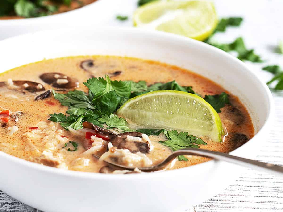 Wicked Thai chicken soup in white bowl with limes and cilantro