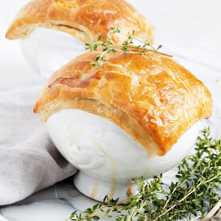 chicken pot pie in white bowls with puff pastry topping