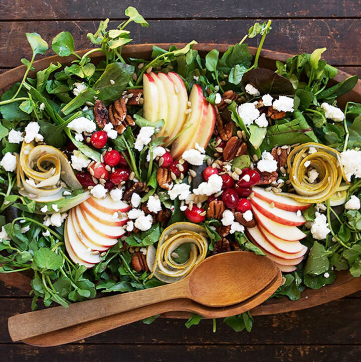 Fall harvest salad in wooden salad bowl with wooden spoons