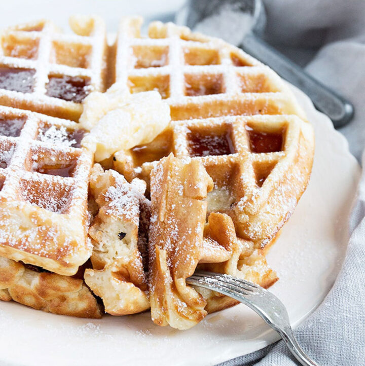 waffles on plate with butter, cut with fork