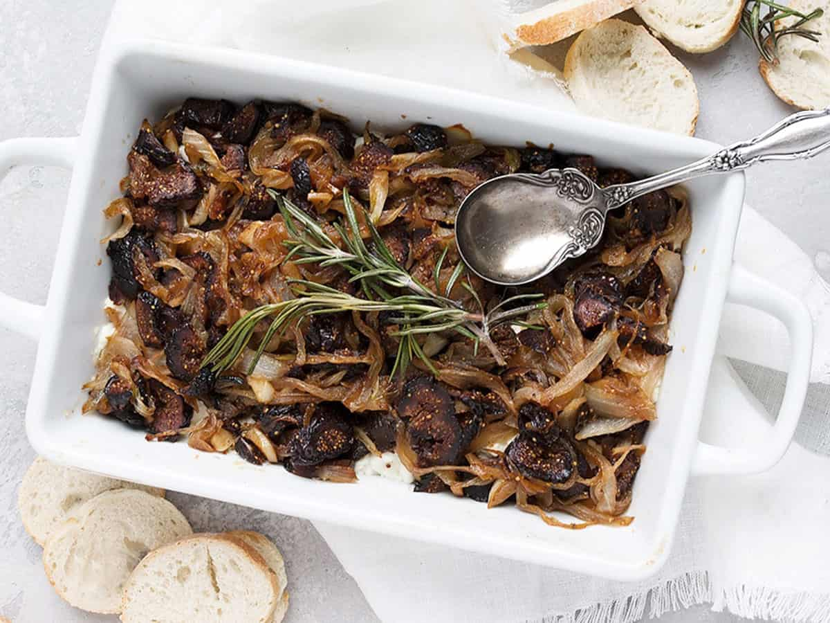 fig onion and goat cheese dip in white dish with spoon