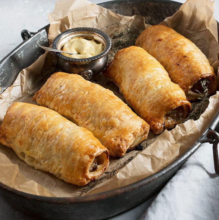 homemade sausage rolls on platter with mustard