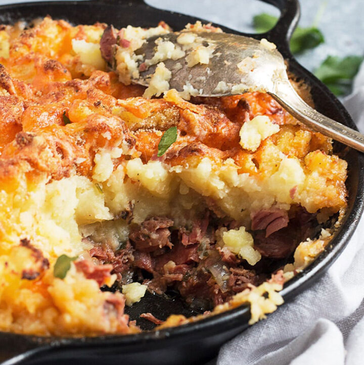corned beef cottage pie in cast iron skillet with spoon