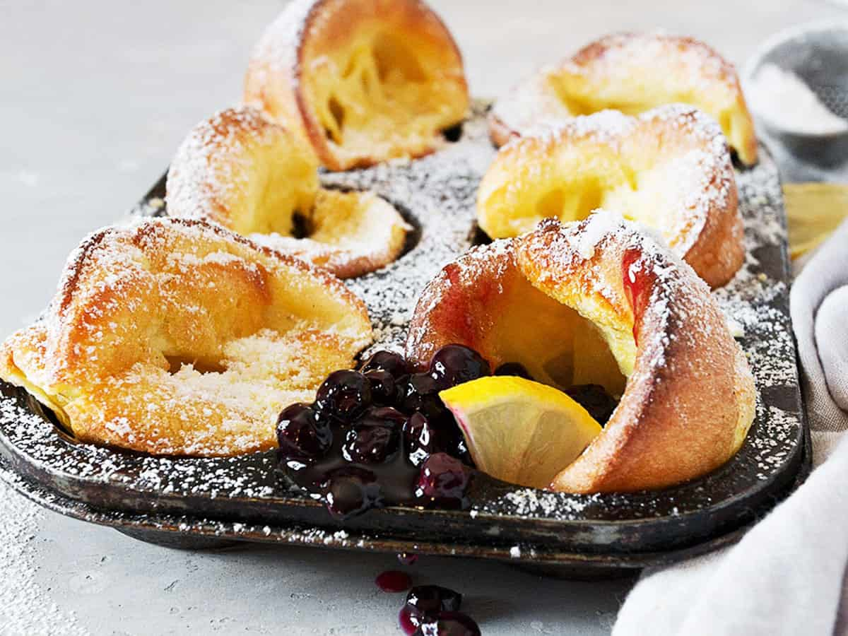 mini Dutch babies in muffin tin with lemons and blueberry sauce