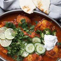 butter chicken thighs in pan with garnishes and naan