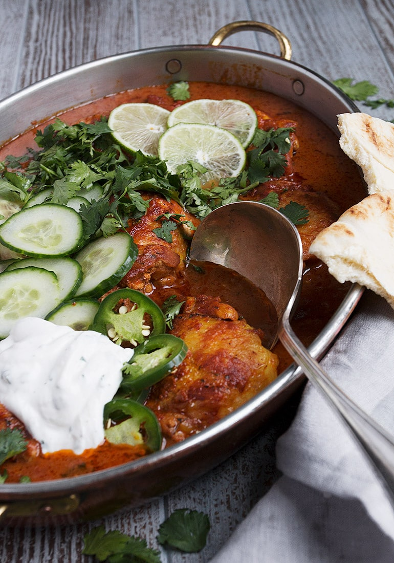 butter chicken thighs in pan with garnishes and Naan bread