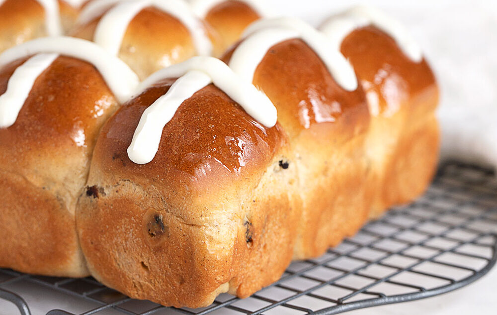 hot cross buns on cooling rack with icing cross