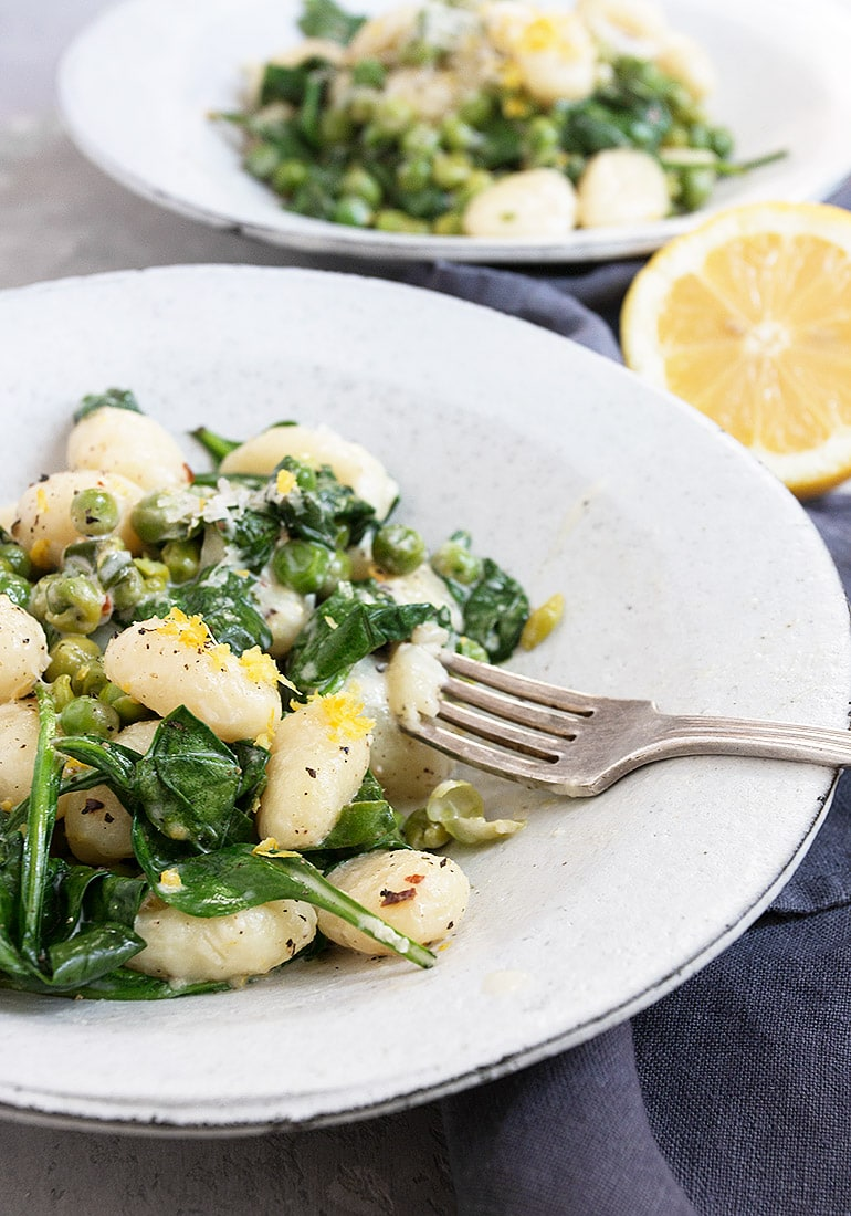 gnocchi with peas, spinach and lemon in a bowl
