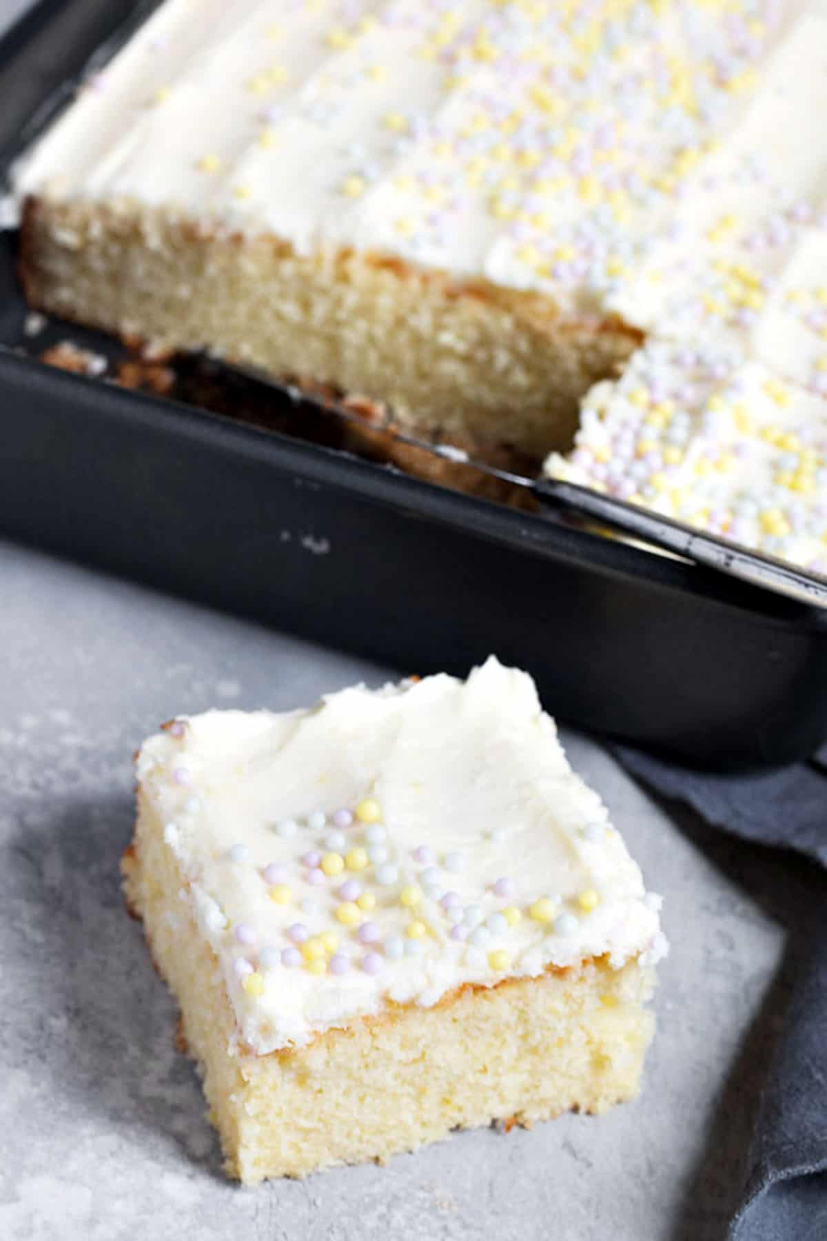 lemon sheet cake with one piece cut out