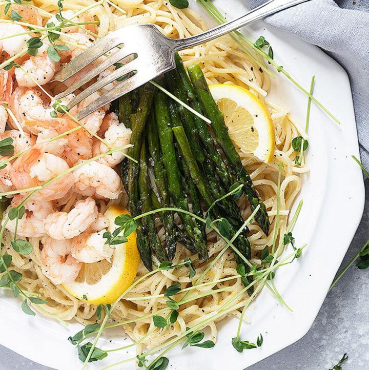 lemon pasta with shrimp and asparagus on white platter