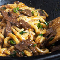 mongolian beef and udon noodles in cast iron wok