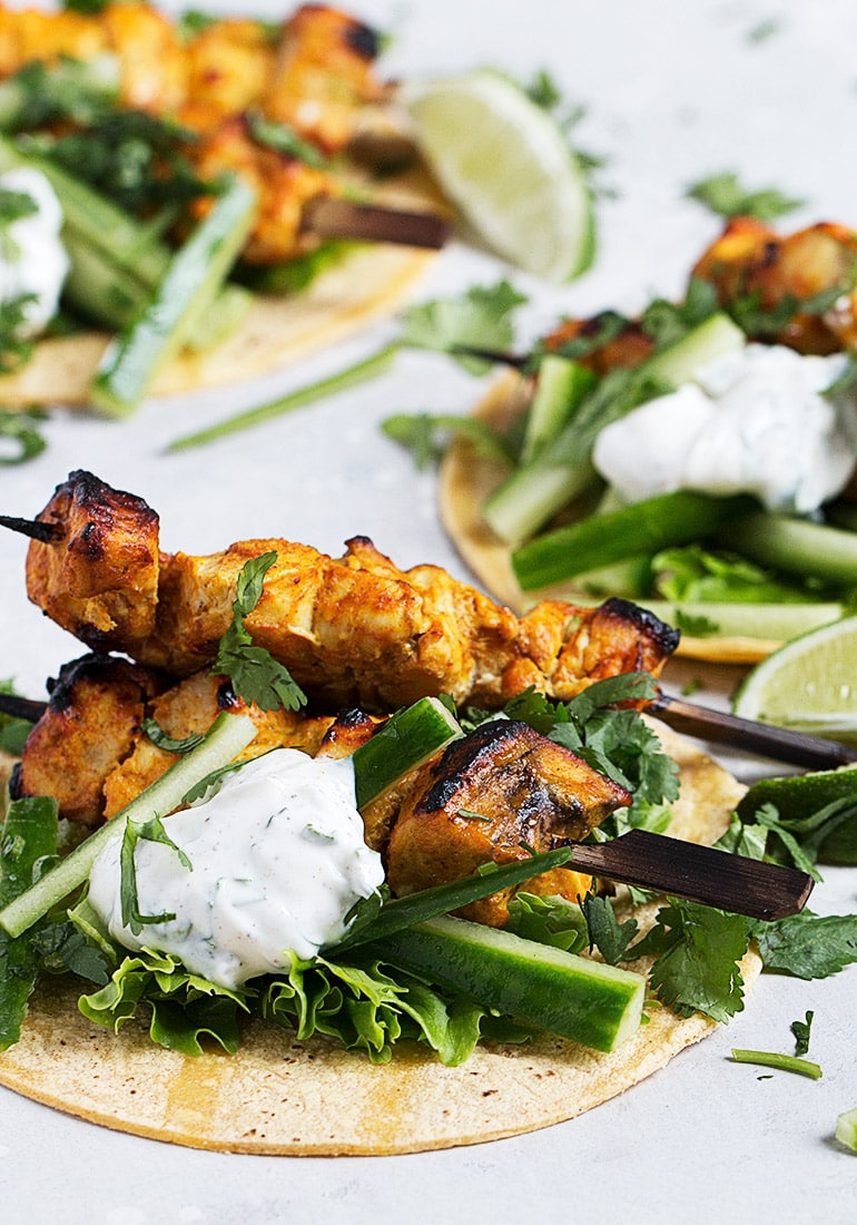 chicken tikka on skewers on top of greens and tortillas