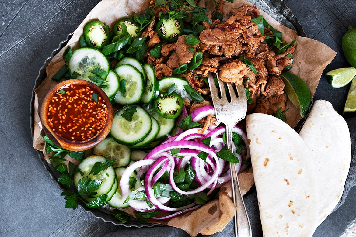 spicy pork in pan with toppings and tortillas