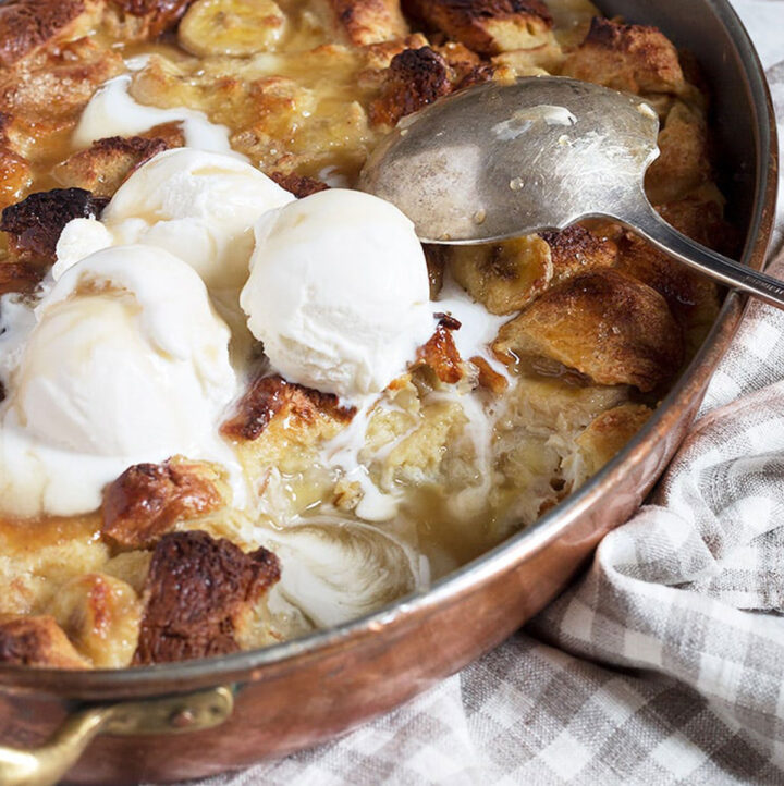bananas foster bread pudding in copper baking pan with ice cream