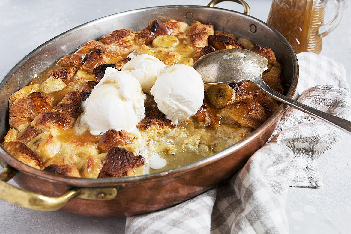 bananas foster bread pudding in pan with spoon